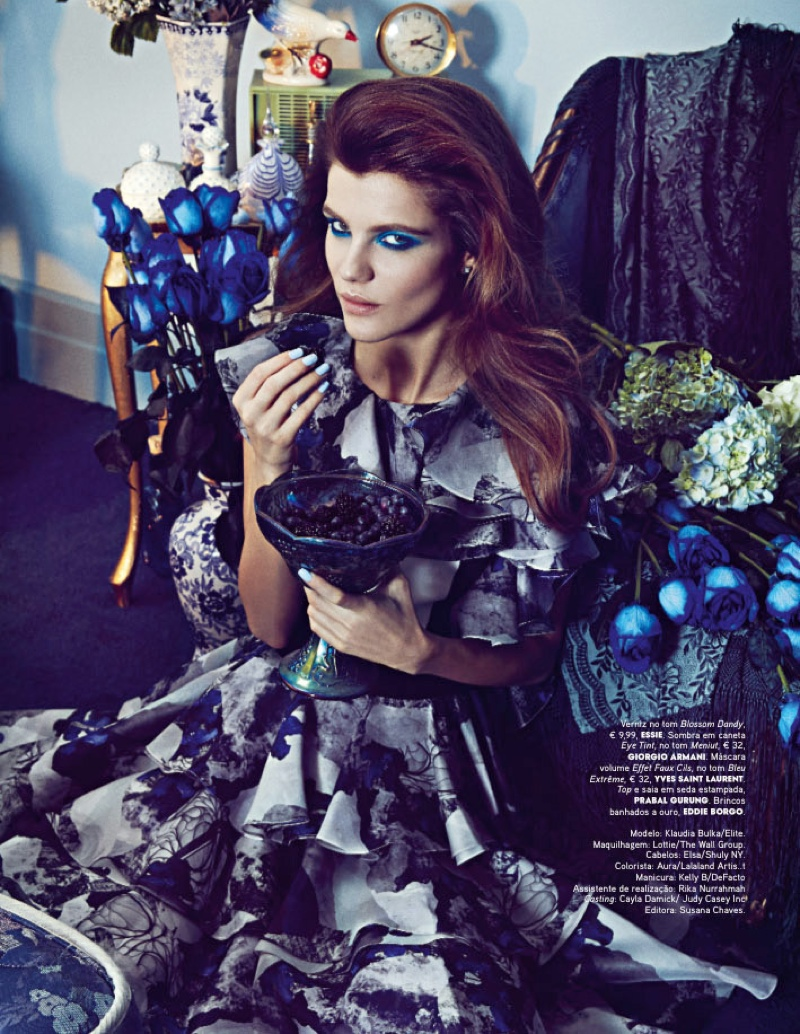 Surrounded by blue flowers, the model wears a floral print dress from Prabal Gurung