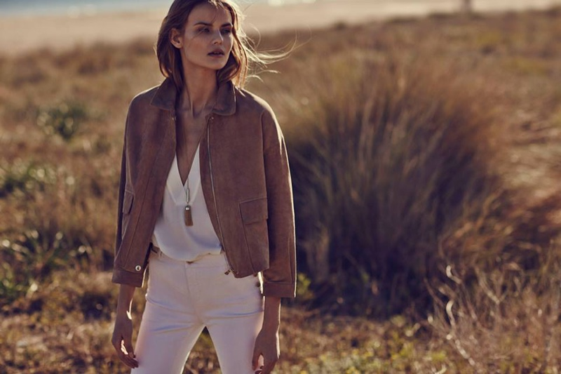 Kate wears a cropped jacket with a white top and pants