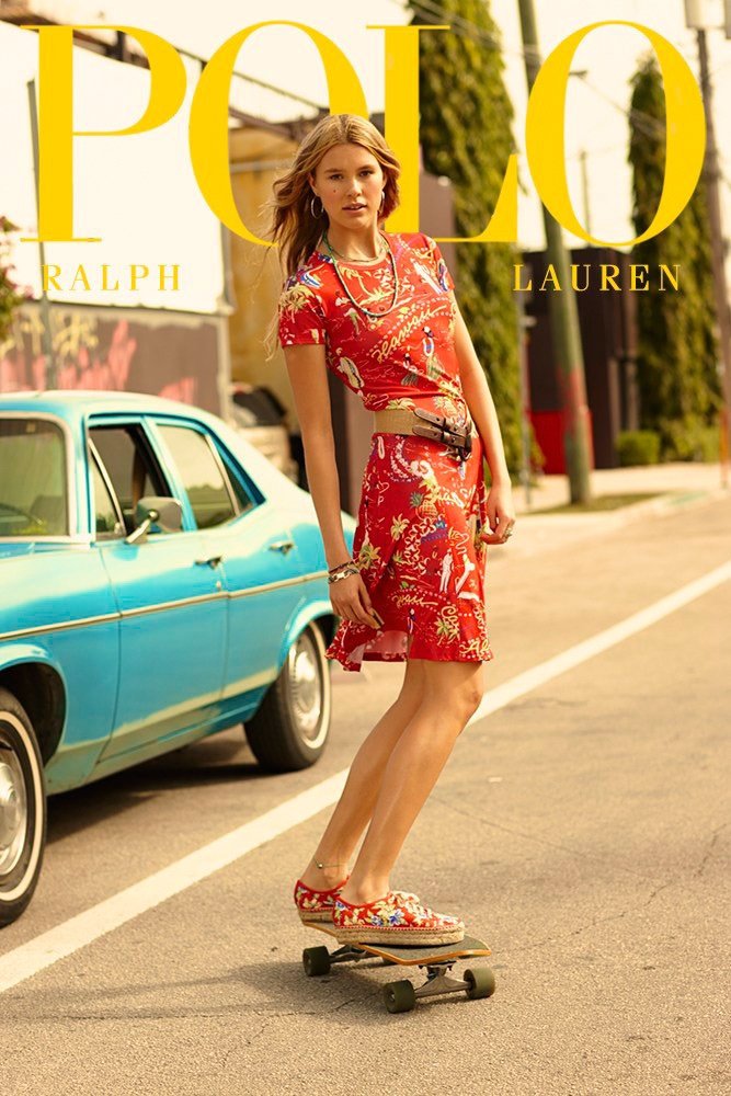 The model wears a dress with a Hawaiian print
