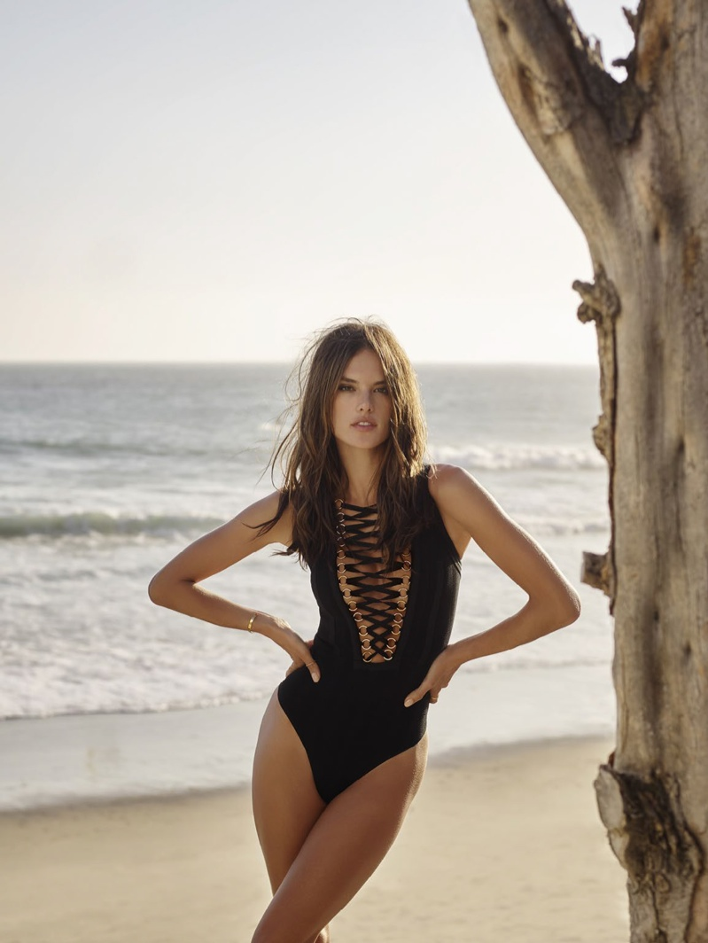 Alessandra wears a black one-piece swimsuit with cut-out details