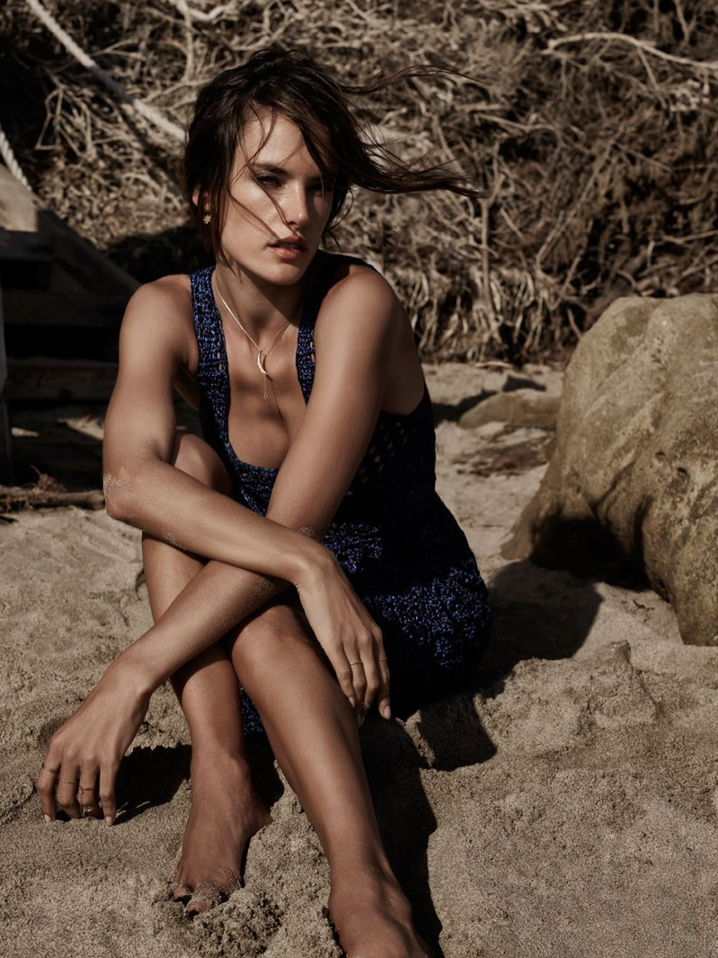 Sitting in the sand, the Brazilian model is a summer vision