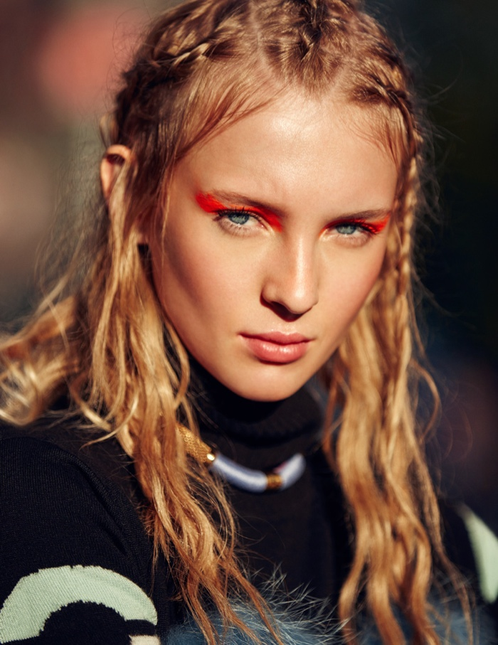 The model wears her hair in beachy waves for this closeup shot