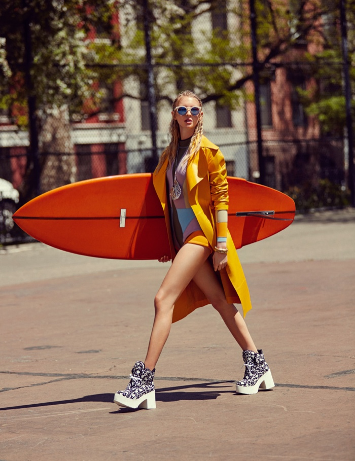 Nastya walks the streets with a surf board in hand