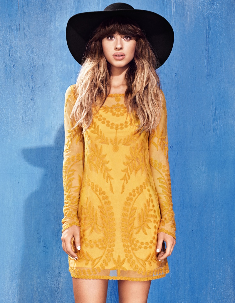 Foxes wears a wide-brimmed hat with a yellow print dress