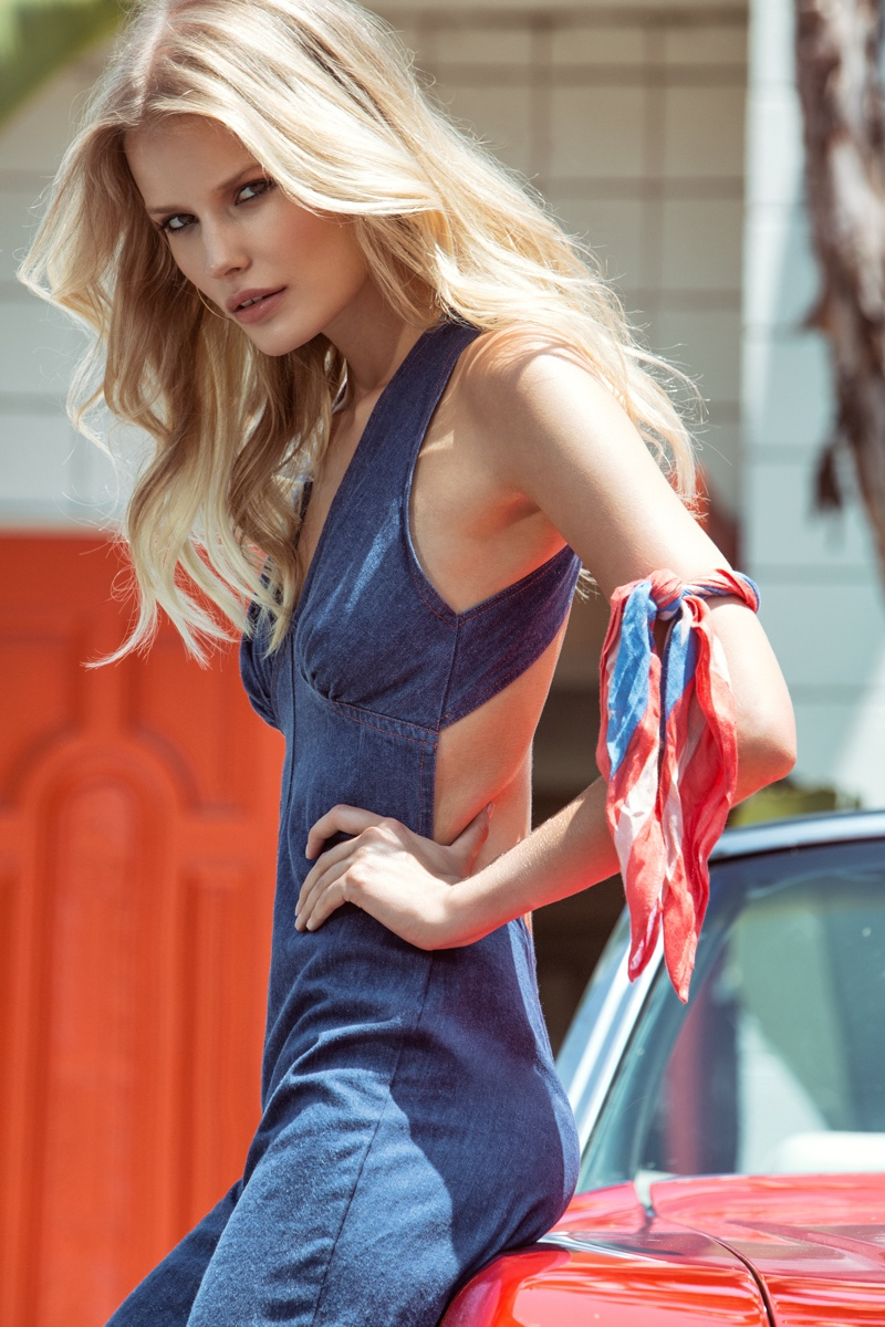 Alena models a a denim jumpsuit with a back cutout