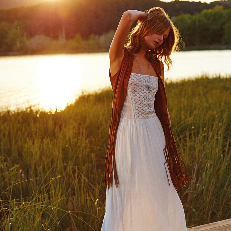 Frida models a fringe adorned dress with a white maxi dress
