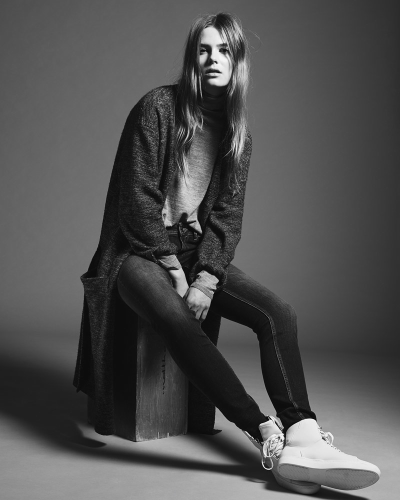 The model wears slim-fit denim paired with and oversized sweater