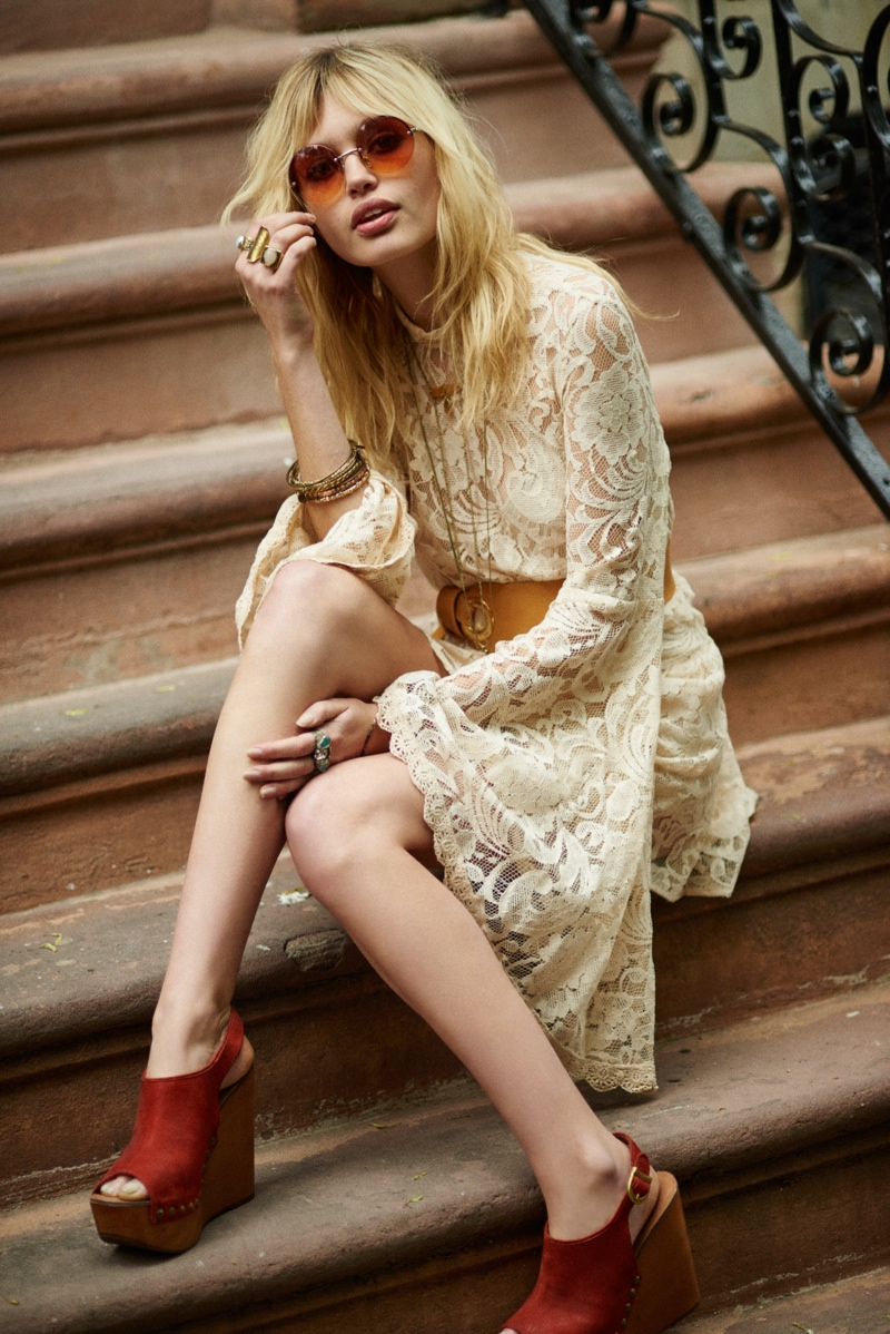 Staz poses in a white lace dress on stoop steps