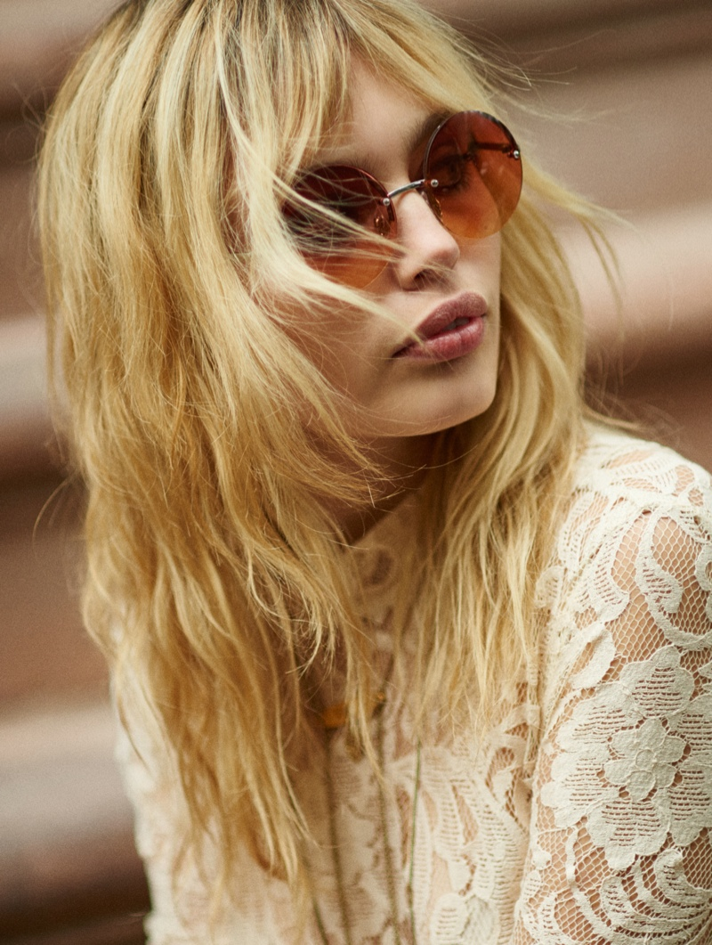 The model wears oversized brown shades for the perfect summer accesory
