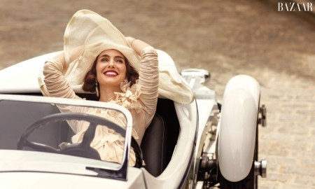 Natalie poses in a convertible car while wear a dress by Givenchy