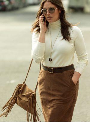 Candice wears white turtleneck, brown skirt and fringe embellished bag