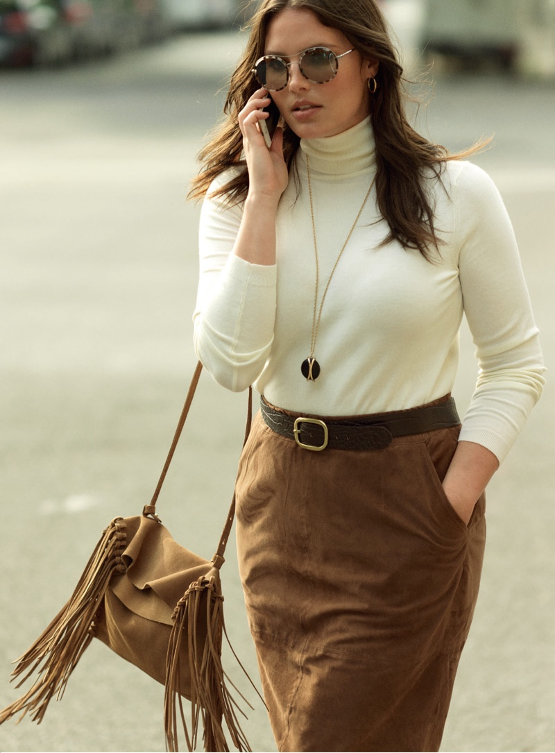 Candice wears white turtleneck, brown skirt and fringe embellished bag