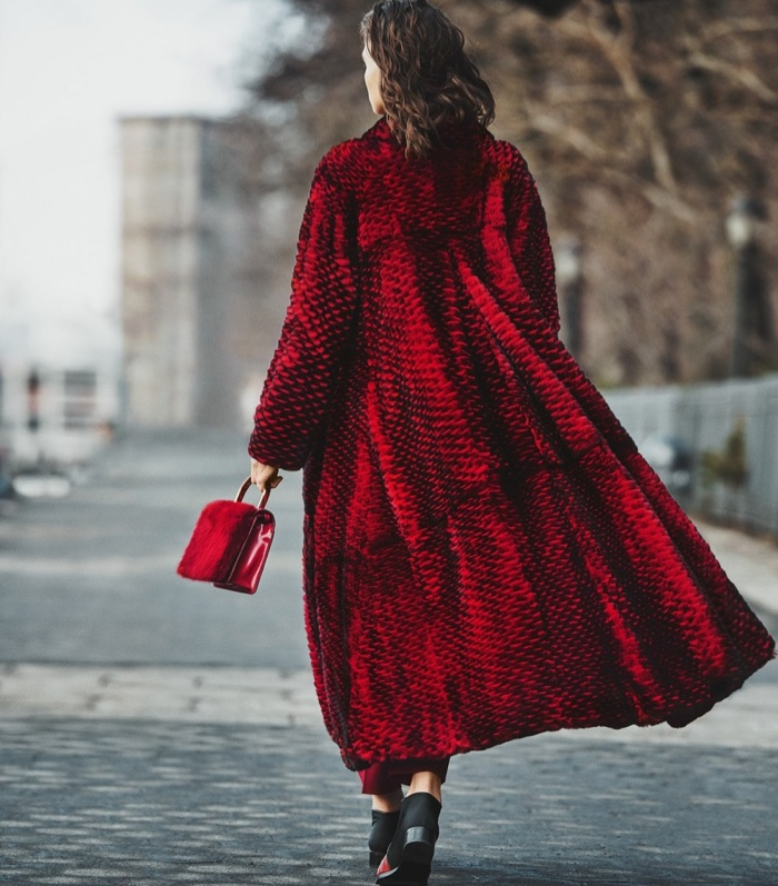 The model wears a fur coat in red