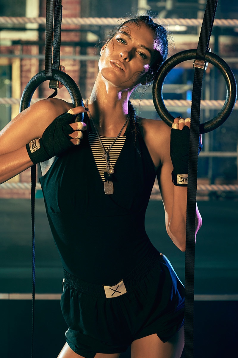 The model flaunts her lithe figure on pull-up rings