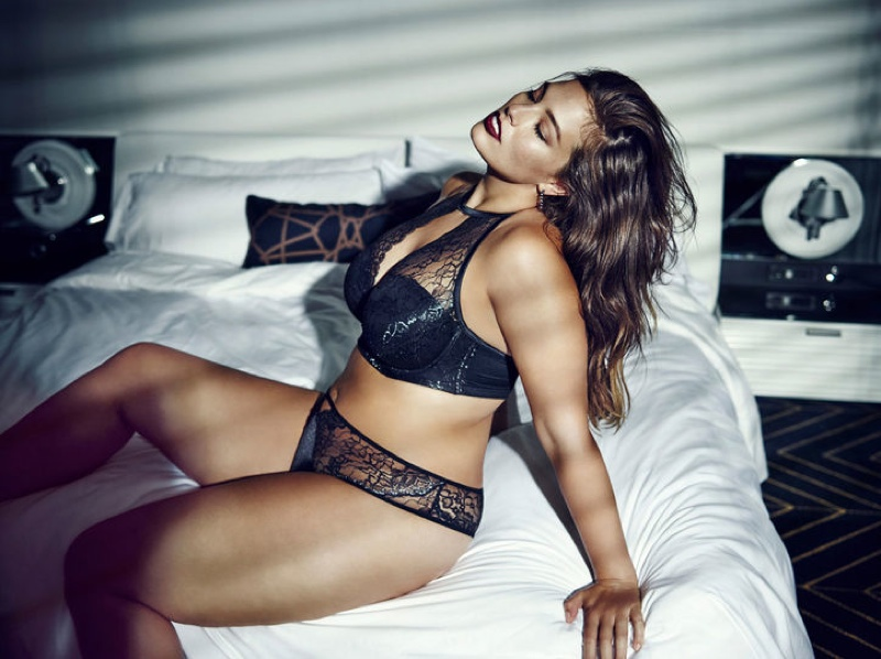 Ashley Graham poses in bed in a sexy black bra and top look