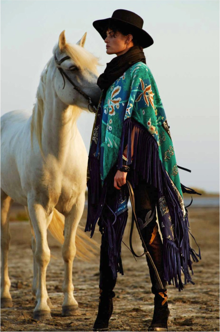 Isabeli poses alongside a horse in a fringed number