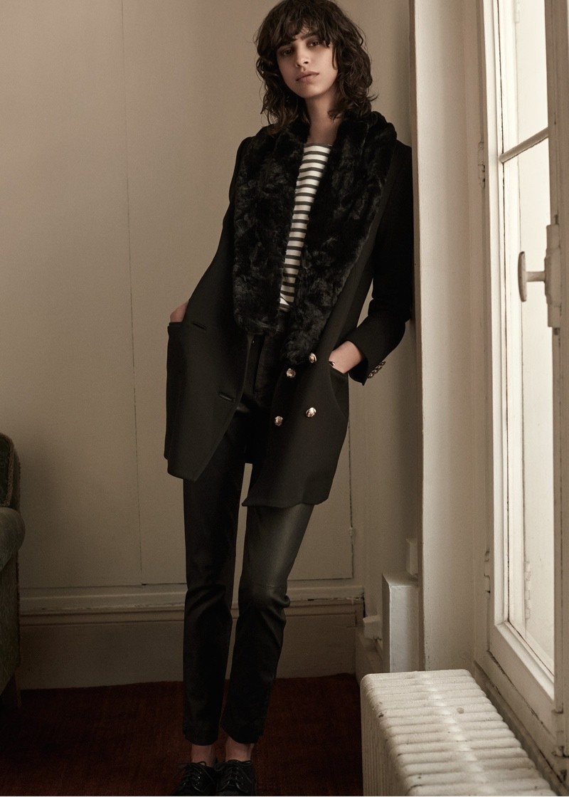 The model wears faux fur coat, striped shirt and slim-fit pants from Mango