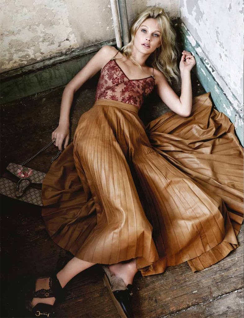 The model wears a pleated skirt and camisole top from Gucci