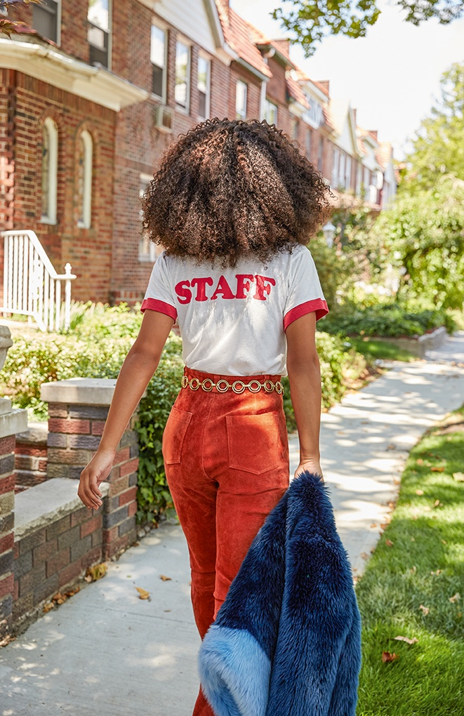 Serayah wears high-waist pants with a tee that reads 'STAFF' on the back