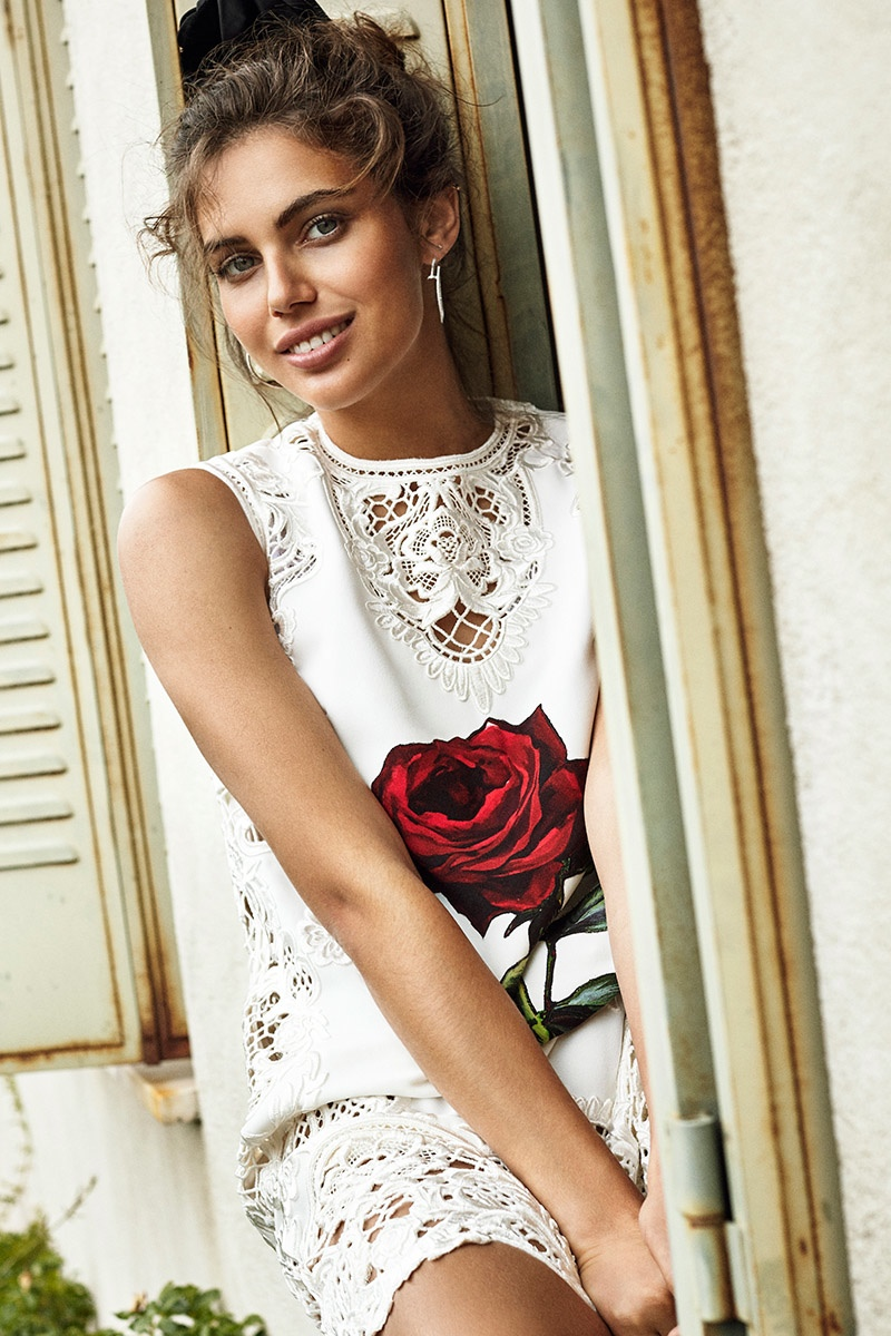Shlomit wears a white dress with a red rose detail