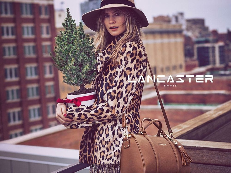 Behati poses in a leopard print jacket and brown tote from Lancaster