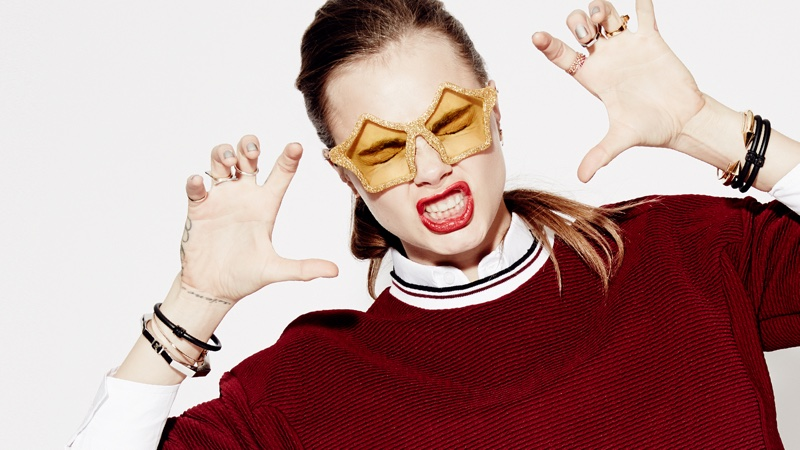 Cara makes a growling face with star-shaped sunglasses