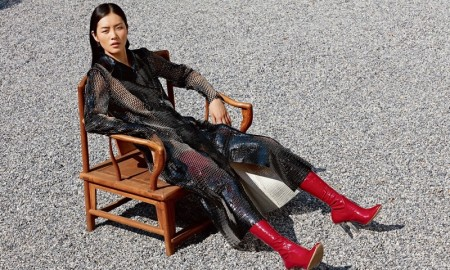 Liu models a black, lacquered leather Dior coat
