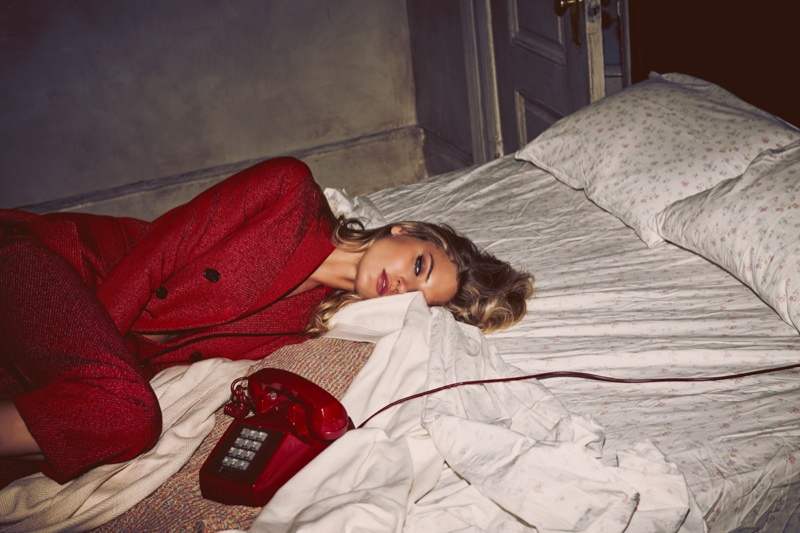Martha poses in bed wearing a red suit jacket