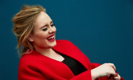 The singer is all smiles in a red cardigan jacket