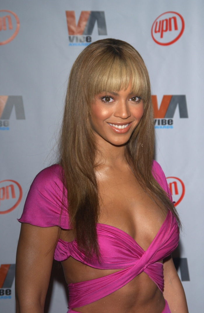 Beyonce pictured with a long honey blonde hairstyle featuring full bangs at the 2003 Vibe Awards. Photo: Featureflash / Shutterstock.com
