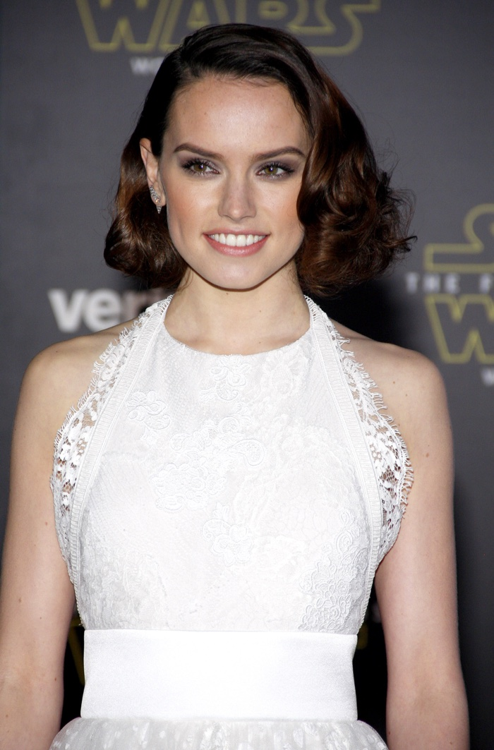 Actress Daisy Ridley with medium length brunette hairstyle featuring tight curls and side part. Photo: Tinseltown / Shutterstock.com