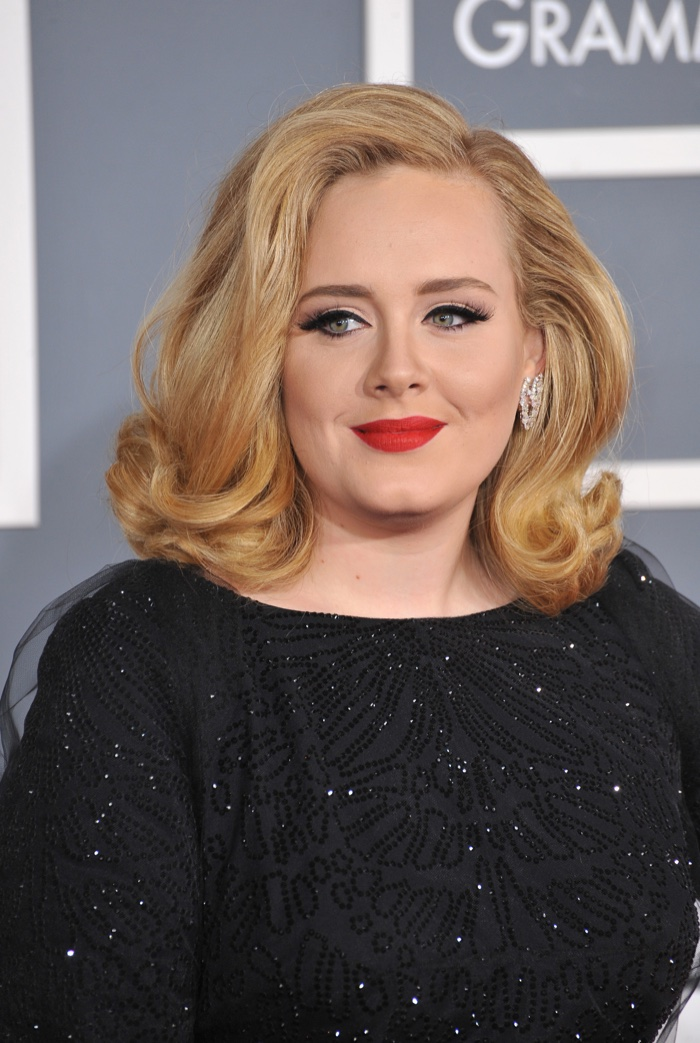 Adele poses with medium length hairstyle featuring flipped curls and side part. Photo: Featureflash / Shutterstock.com