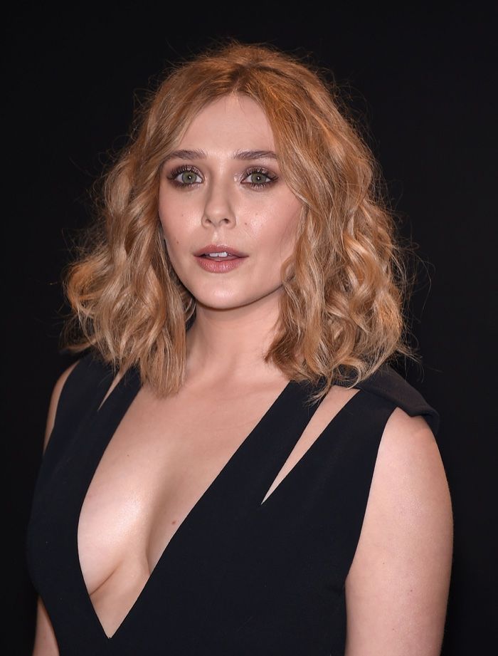 Elizabeth Olsen wears wavy medium-length hairstyle with center part. Photo: DFree / Shutterstock.com