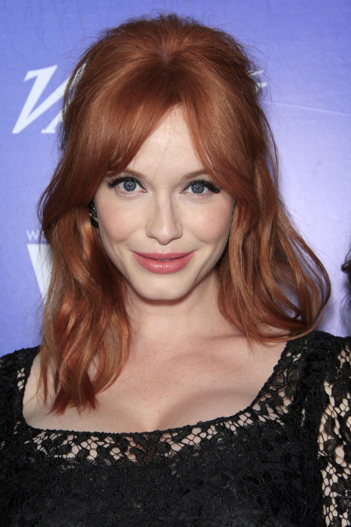 Redhead Christina Hendricks wears wavy half up, half down hairstyle for medium length hair with parted bangs. Photo: Helga Esteb / Shutterstock.com