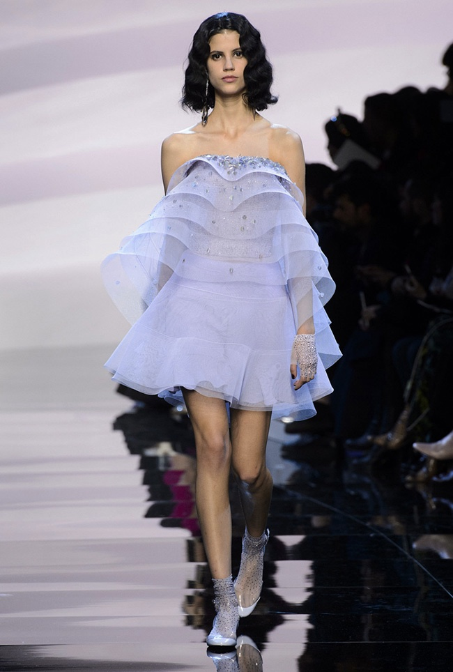 A model walks the runway at Armani Prive's spring 2016 haute couture runway show wearing a mini dress with ruffles