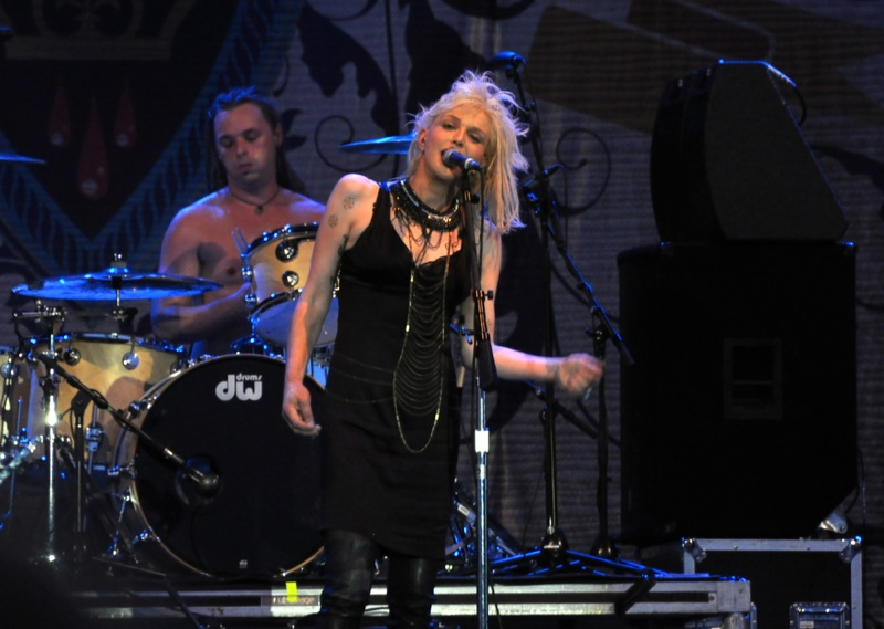 2010: Courtney Love performs on stage with her band Hole, wearing a black dress and matching choker. Photo: Paul McKinnon / Shutterstock.com