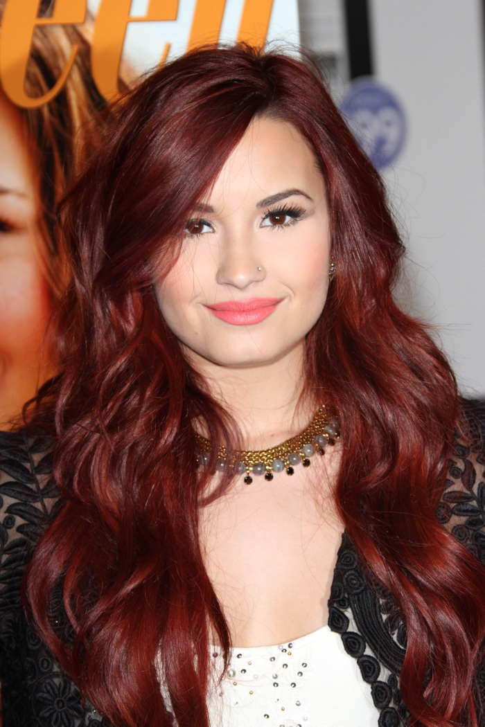 Demi Lovato displays the dark red hair color with gorgeous and long, mermaid waves.