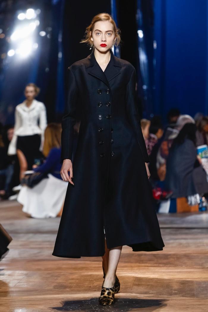 A model walks Dior's spring 2016 show in black coat with flared hem