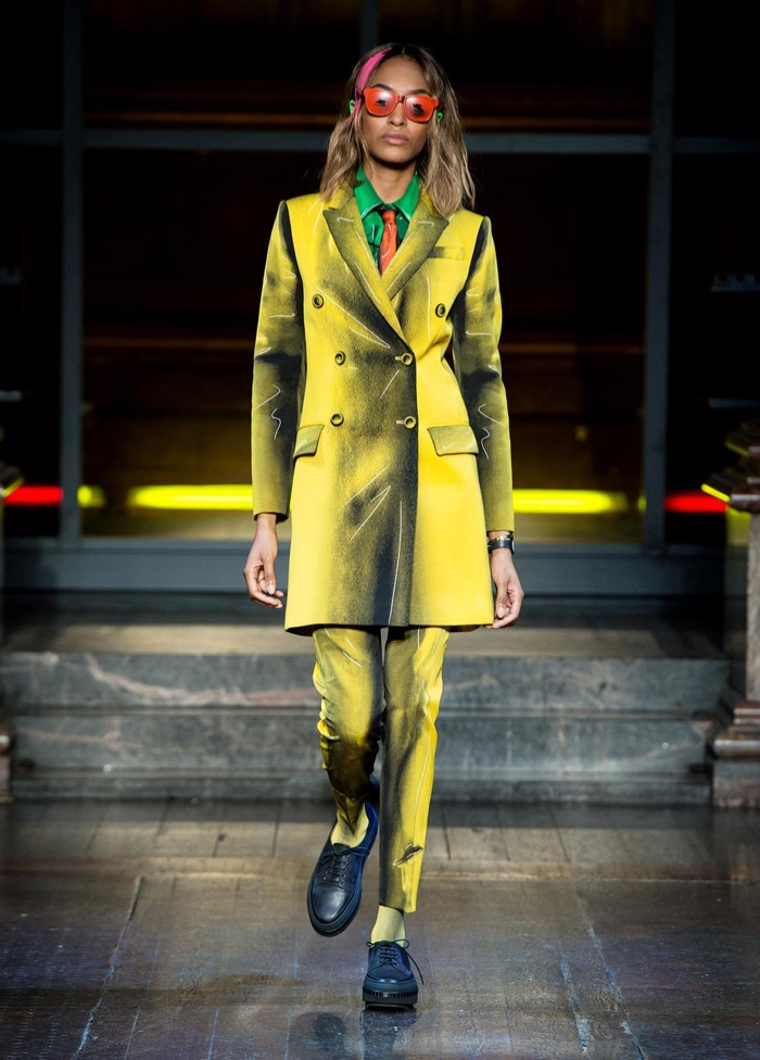 SUITING UP: Jourdan Dunn walks the runway at Moschino's fall-winter 2016 show wearing a yellow pant suit with graphic detail