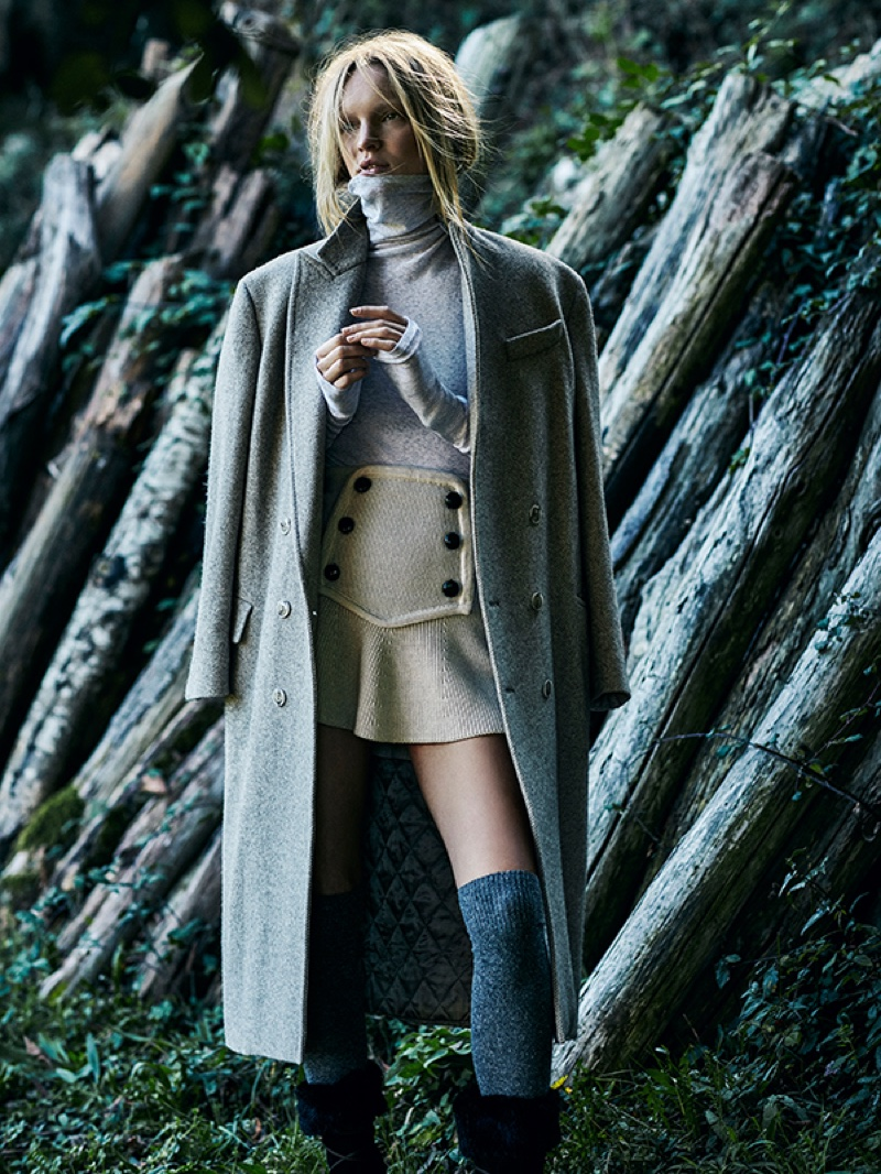 A long coat layered over a turtleneck and mini skirt makes a statement
