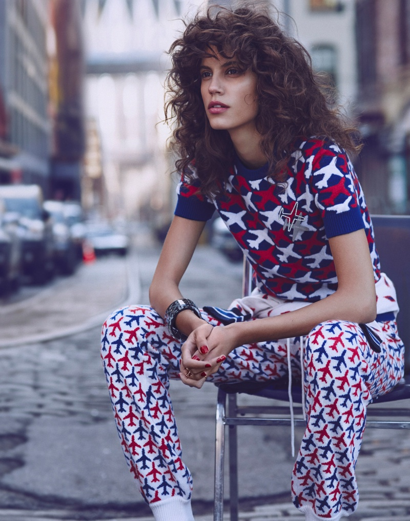 Sitting down, Antonina models a Chanel sweater and trousers with a plane print