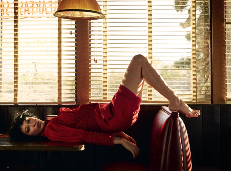 Posing in a diner, Bella lays on a table in a red blouse and shorts designed by Fendi