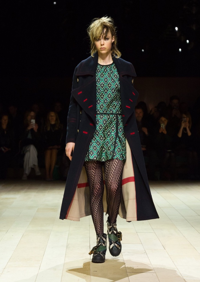 Edie Campbell walks the runway at Burberry's fall-winter 2016 show wearing a military coat and metallic diamond jacquard pleated shirt dress
