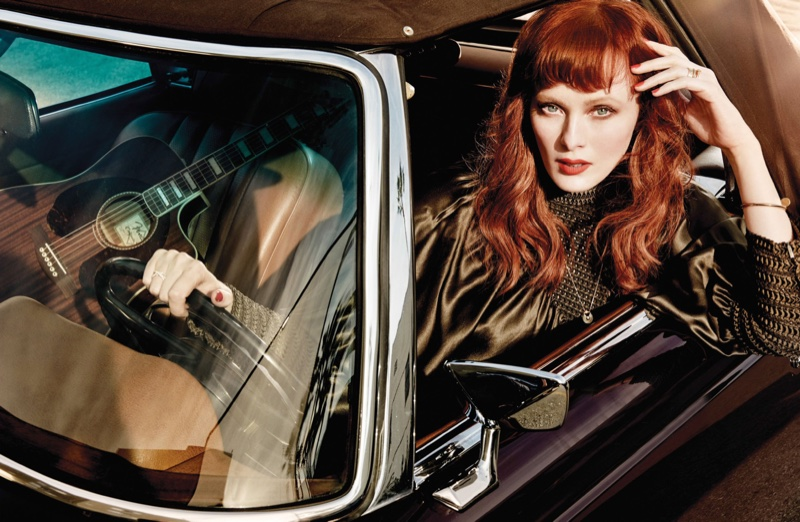 Posing behind the wheel of a car, Karen Elson models a black blouse with puffy sleeves