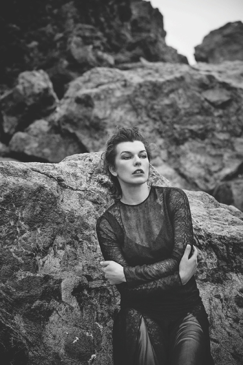Milla Jovovich poses beachside in a sheer lace look for the shoot
