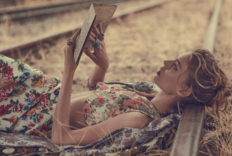 The model lounges in a floral crop top and skirt as she reads a book