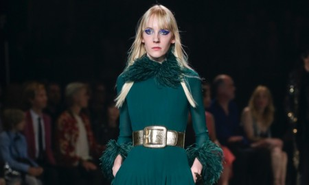 Model wears long-sleeve green maxi dress with wide gold belt at Saint Laurent's fall 2016 runway show