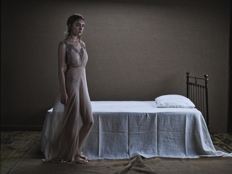 Photographed next to a bed, Saoirse Ronan wears a sheer Rosamosario dress