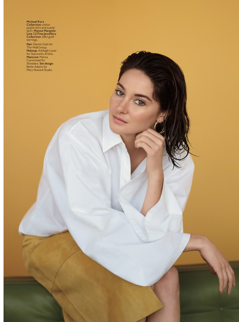 Shailene sits in a casual look from Michael Kors Collection with a white shirt and brown suede skirt
