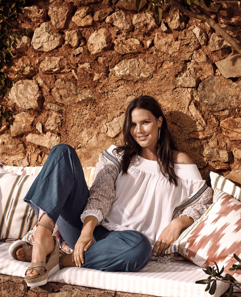 Candice Huffine lounges in an off-the-shoulder top and denim jeans